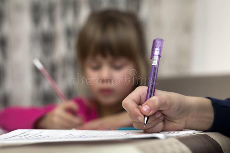Портрет милого милого маленького серьезного чертежа девушки ребенка с карандашем на бумаге на запачканной предпосылке Образование стоковая фотография rf