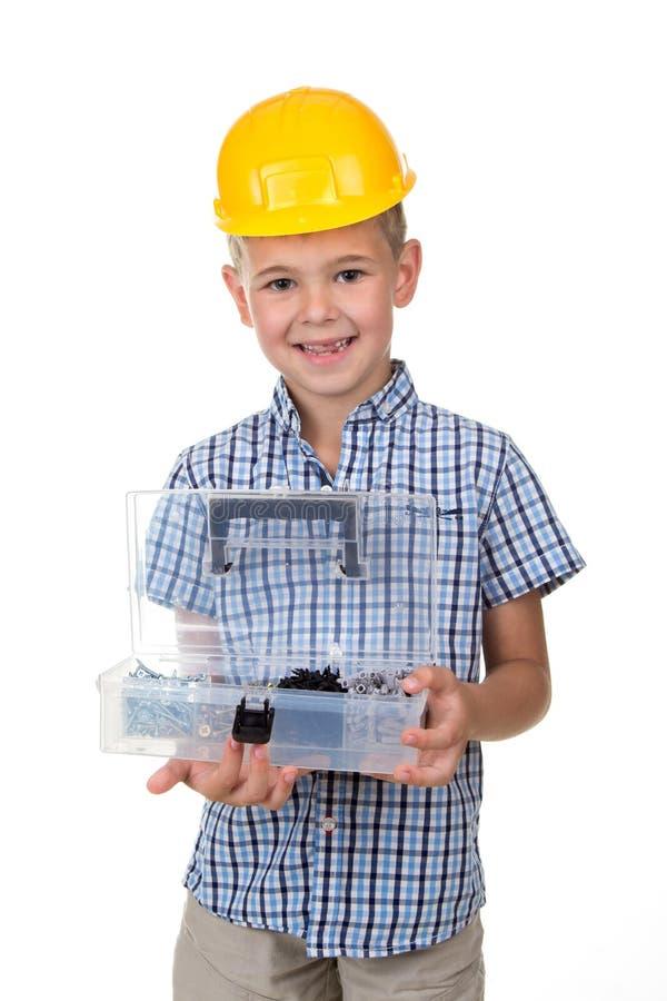 Портрет милого усмехаясь мальчика нося голубую checkered рубашку и желтый защитный шлем, держа раскрытый toolbox, белая предпосыл стоковая фотография