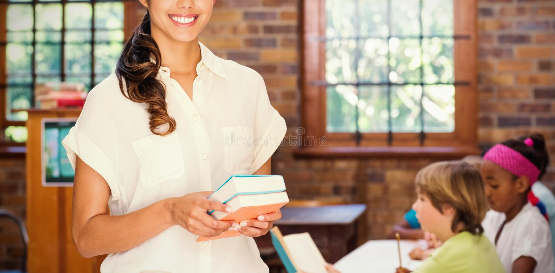 Портрет милого учителя держа книги стоковые фотографии rf