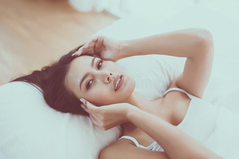 Портрет милой азиатской женщины лежа вниз на спальне, сексуальной женской и идеальной коже, закрывает вверх по стороне стоковые фотографии rf