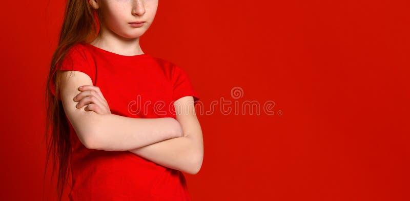 Портрет милой девушки осадил в красном жилете, стоя со сложенными руками и смотря камеру стоковые изображения rf