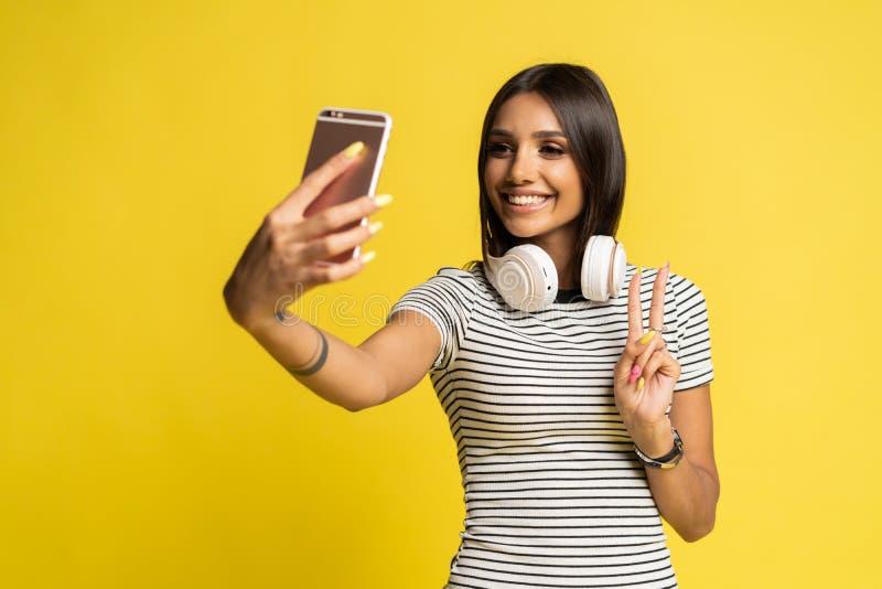 Портрет милой девушки принимая selfie изолированное над предпосылкой цвета стоковые изображения
