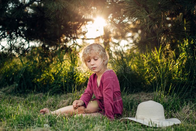 Портрет милой красивой белокурой кавказской девушки в красном розовом платье с грязными untidy волосами сидя на земной траве в па стоковые фотографии rf