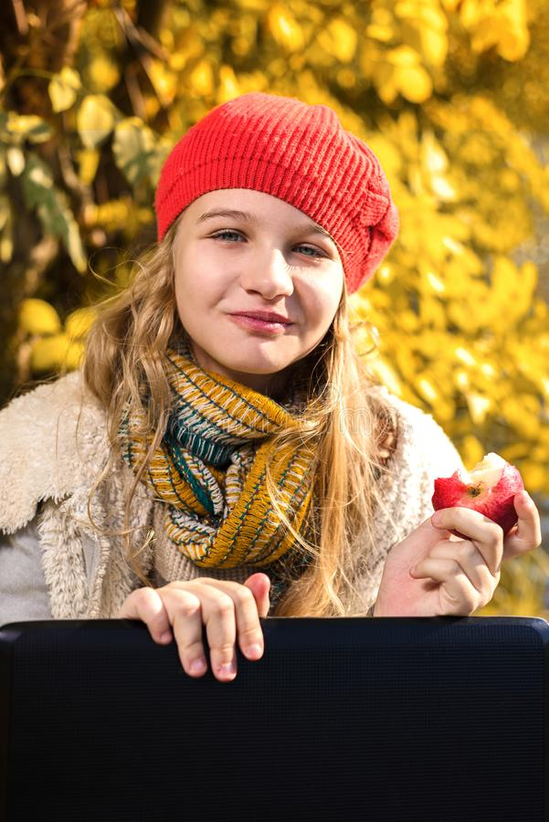 Портрет милой маленькой девочки в красной шляпе есть яблоко и усмехаться стоковая фотография rf