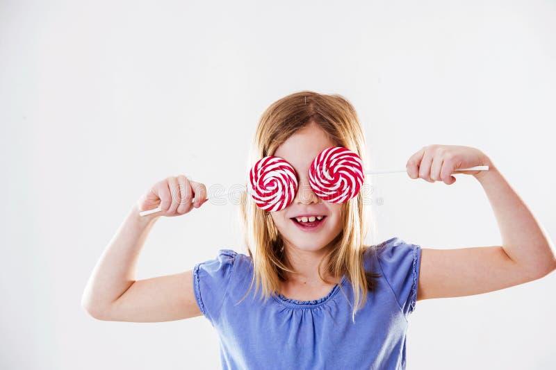 Портрет милой маленькой девочки имея потеху с 2 леденцами на палочке, покрывая ее да с ними стоковое фото
