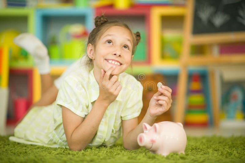 Портрет милой маленькой девочки с копилкой стоковое изображение rf