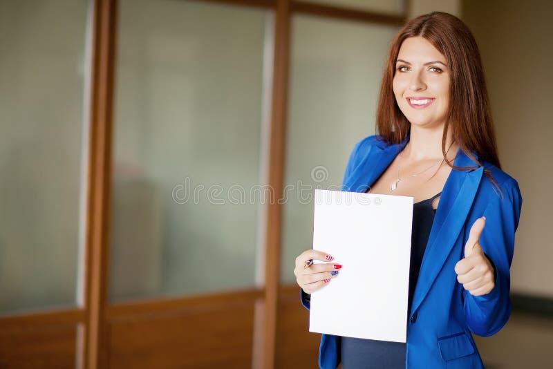 Портрет милой молодой бизнес-леди усмехаясь, в окружающей среде офиса стоковые фотографии rf