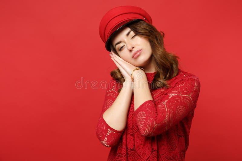 Портрет милой молодой женщины в платье и крышке шнурка спать с руками около стороны изолированной на яркой красной стене стоковая фотография