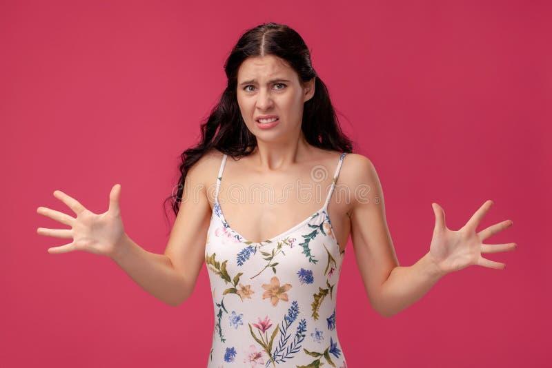 Портрет милой молодой женщины в светлом положении платья на розовой предпосылке в студии Эмоции людей задушевные стоковая фотография