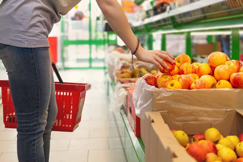 Портрет милой молодой женщины с корзиной в ее руках, которая выбирает яблоки в супермаркете r стоковое фото rf