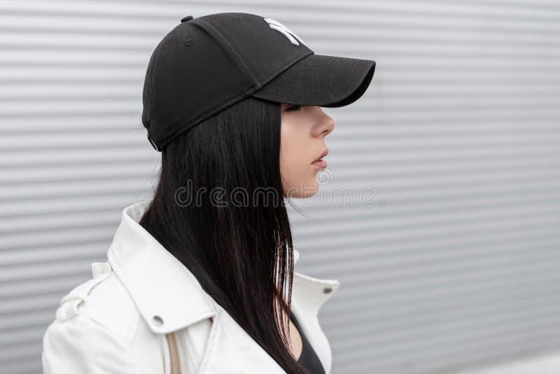 Портрет милой молодой красивой женщины в стильной белой кожаной куртке в модной черной бейсбольной кепке около стены металла стоковое фото