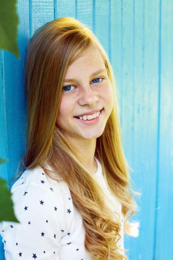 Портрет милой предназначенной для подростков девушки на голубой деревянной предпосылке стены стоковое фото