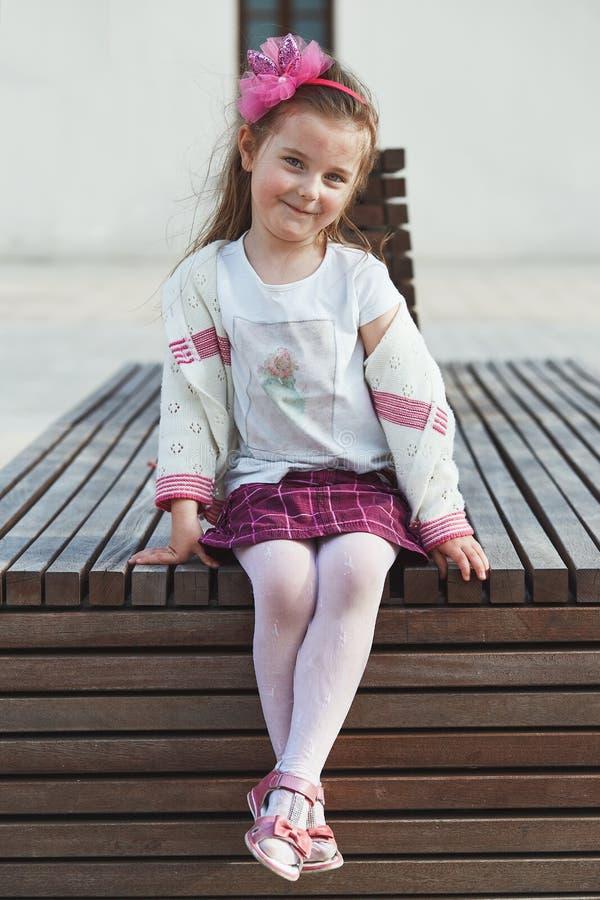 Портрет милой прелестной маленькой девочки сидя на стенде в центре города стоковая фотография
