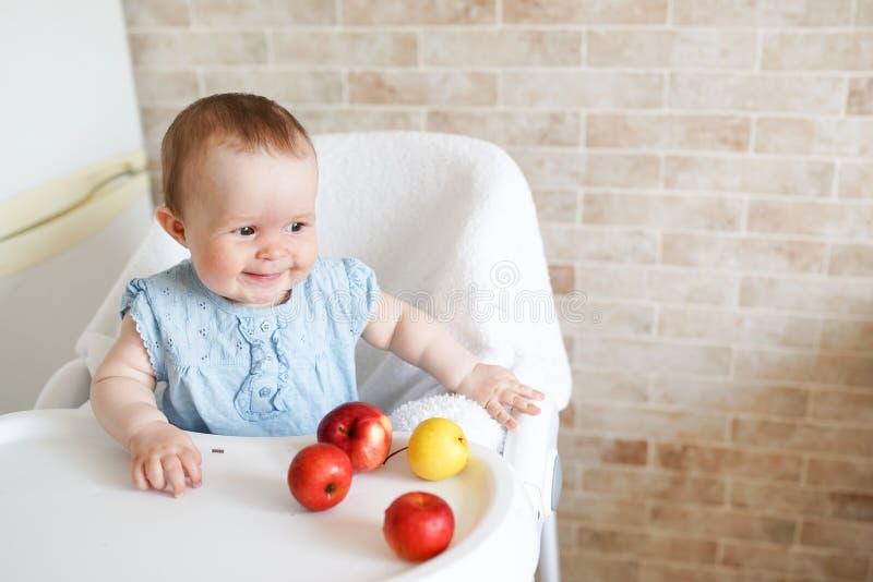 Портрет милой прелестной усмехаясь смеясь кавказской девушки ребенк ребенка сидя в высоком стуле есть плод яблока стоковое фото