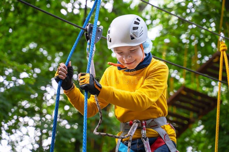Портрет милой прогулки мальчика на мосте веревочки в парке веревочки приключения стоковая фотография