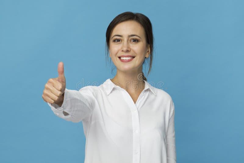 Портрет милой усмехаясь женщины с белый представлять рубашки изолированной на голубой предпосылке стоковое изображение