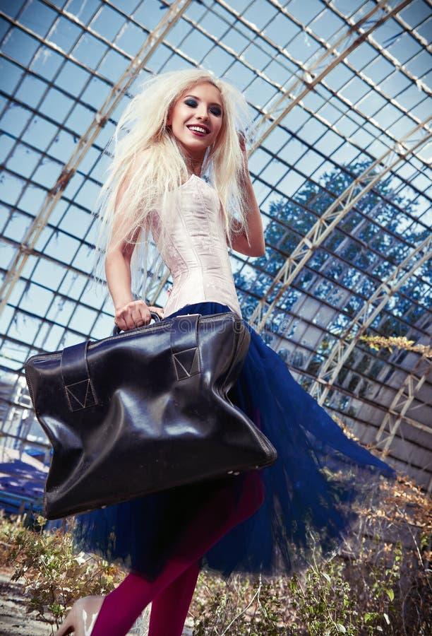 Портрет милой усмехаясь странной девушки с старым чемоданом Корсет привлекательной женщины нося, колготки и юбка балетной пачки в стоковая фотография
