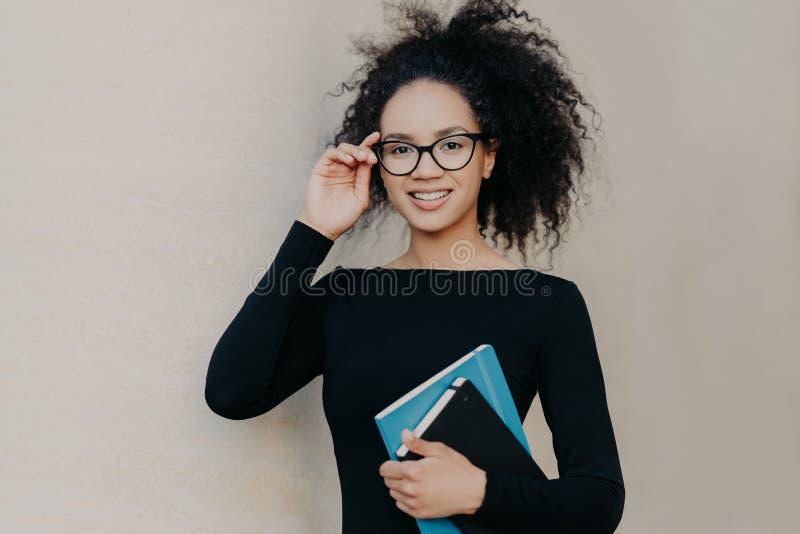 Портрет милой frizzy молодой женщины с нежной улыбкой, держит руку на оправе стекел, носит случайного черного прыгуна, держит бло стоковое изображение rf