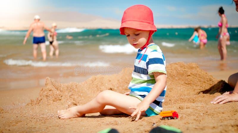 Портрет милых 3 лет старого мальчика сидя на песчаном пляже рядом с морем Ребенок ослабляя и имея потеху на стоковые изображения