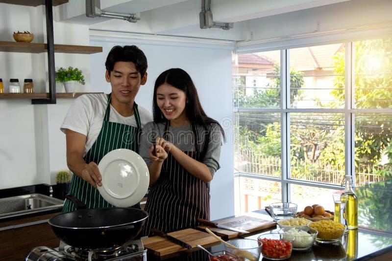 Портрет милых счастливых пар в рисберме в жизнерадостной плите удерживания действия подготавливая варящ завтрак украшенный с ингр стоковое фото