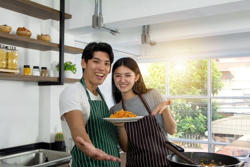 Портрет милых счастливых пар в рисберме в жизнерадостном гордо представляющ завтрак таблицы макарон украшенный с ингредиентом  стоковые фотографии rf
