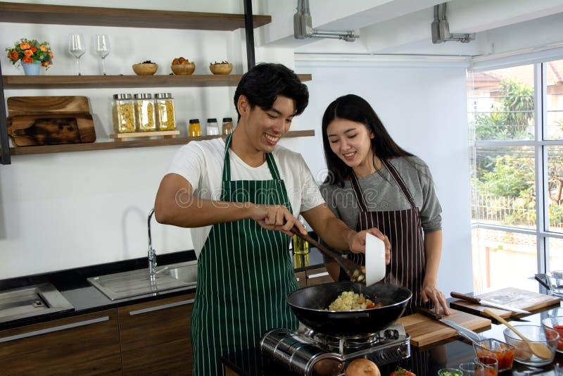 Портрет милых счастливых пар в рисберме в жизнерадостном действии подготавливая завтрак и добавляя макароны и другой ингредиент у стоковое изображение rf