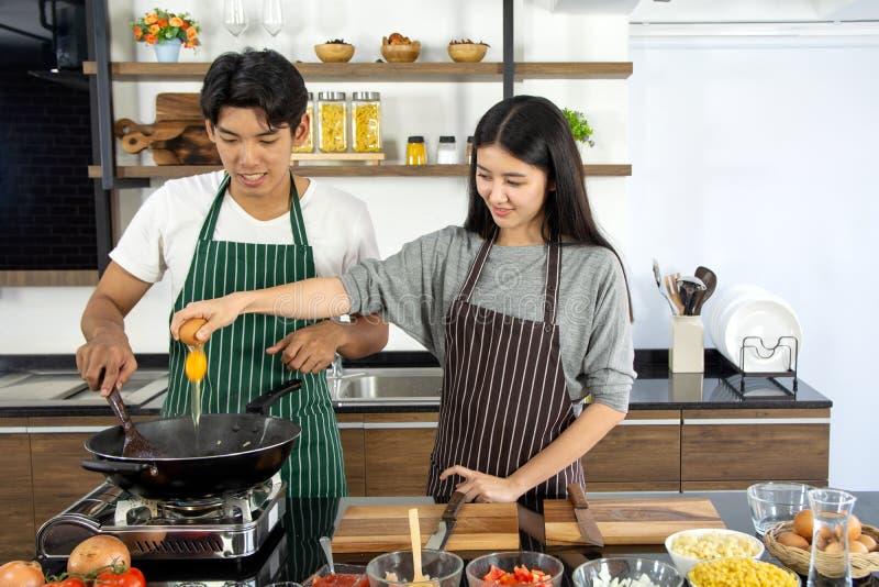 Портрет милых счастливых пар в рисберме в жизнерадостном действии подготавливая даму завтрака добавляя яйцо украшенное с ингредие стоковое фото