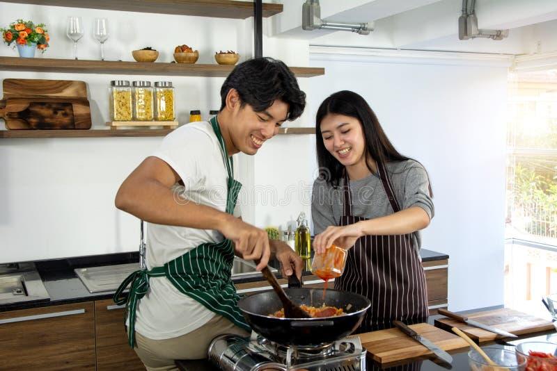 Портрет милых счастливых пар в рисберме в жизнерадостном действии подготавливая завтрак добавляя ингредиент для того чтобы сделат стоковая фотография