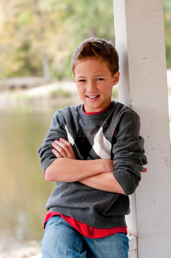 Портрет милого мальчика сидя в газебо при пересеченные руки стоковое изображение