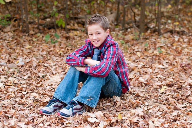 Портрет милого мальчика сидя в листьях при пересеченные ноги стоковое изображение