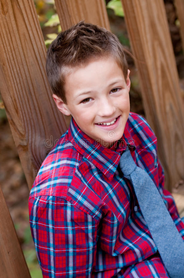Портрет милого мальчика сидя рядом с мостом outdoors стоковые фотографии rf