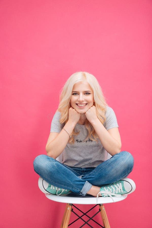 Портрет милой белокурой женщины сидя на стуле стоковая фотография