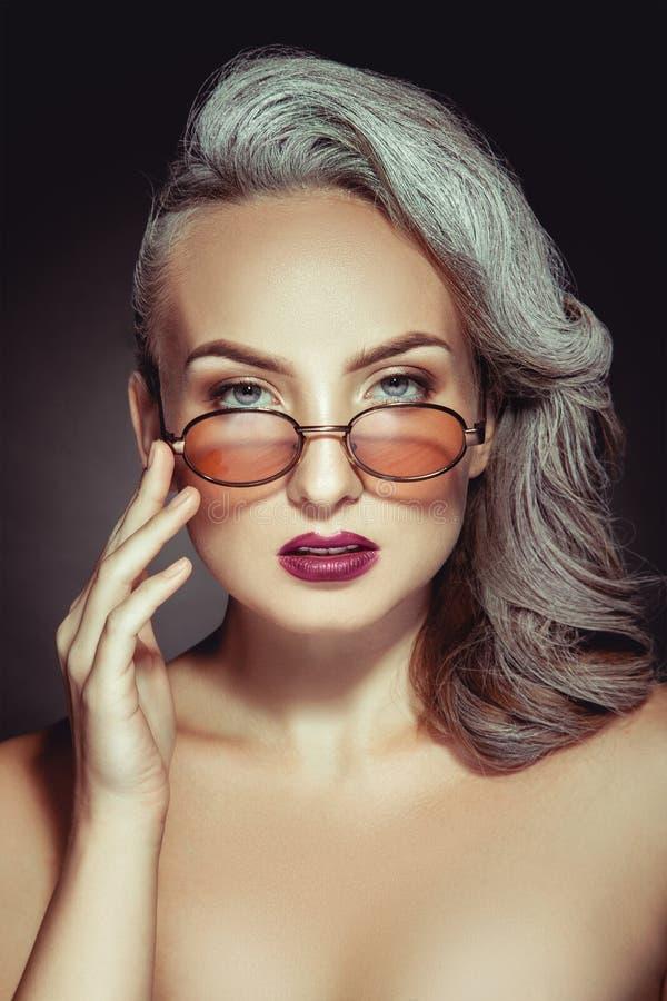 Портрет милой женщины в стильных солнечных очках с серым colo волос стоковые фото