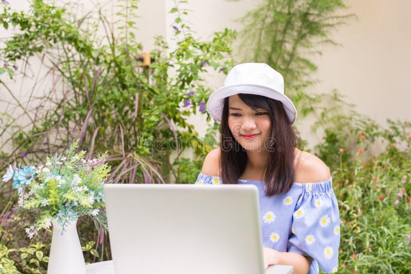 Портрет милой молодой женщины работая на ее компьютере на террасе ее дома стоковая фотография rf