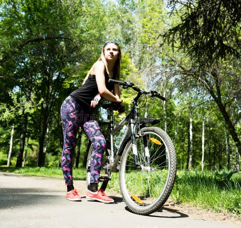 Портрет милой молодой женщины с велосипедом в парке - внешнем стоковые изображения