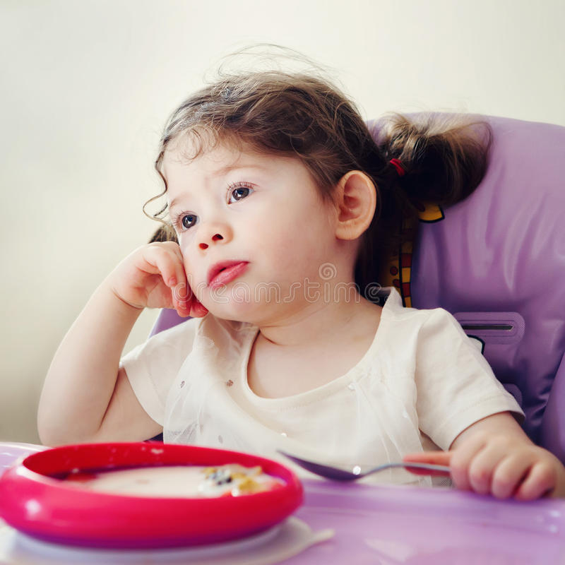 Портрет милой пробуренной кавказской девушки ребенк ребенка сидя в высоком стуле есть хлопья с ложкой рано утром стоковое изображение rf
