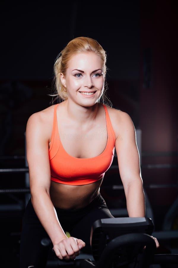Портрет милой славной женской разминки на фитнесе темнота велотренажера на спортзале стоковые фото