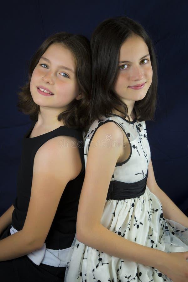 Портрет 2 милых сестер спина к спине стоковое фото rf