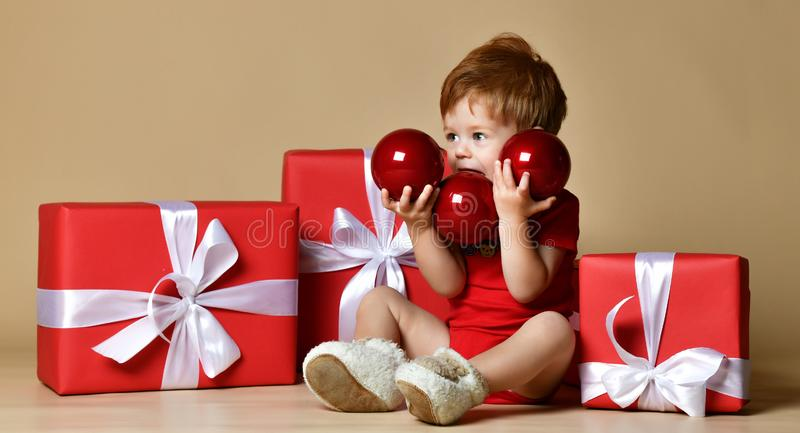 Портрет младенца одел красный bodysuit с красными украшениями шариков на подарках xmas присутствующих над бежевой обнаженной пред стоковое фото