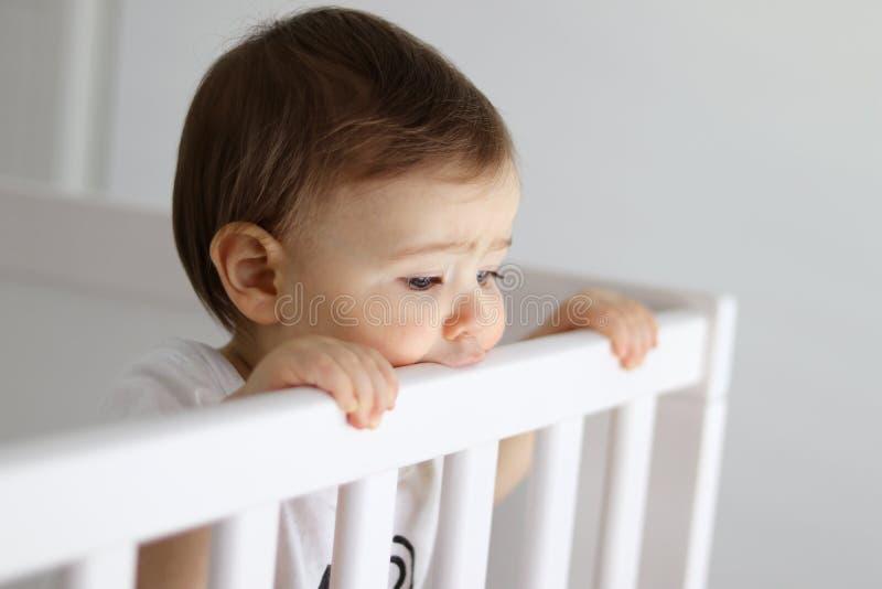 Портрет младенца оставаясь в его кроватке младенца смотря уныло стоковое изображение rf