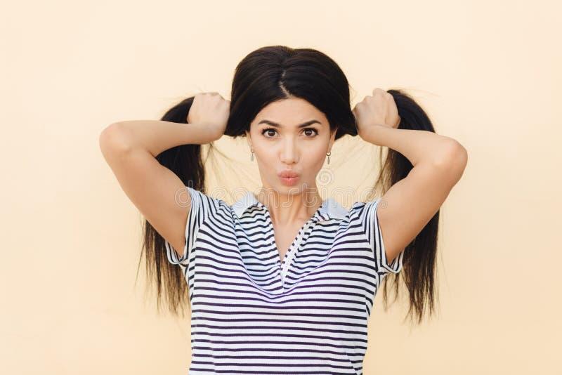 Портрет модели милого брюнет женской делает 2 хвоста от ее роскошных волос, имеет темные глаза, держит круг губ, носит casu стоковое изображение