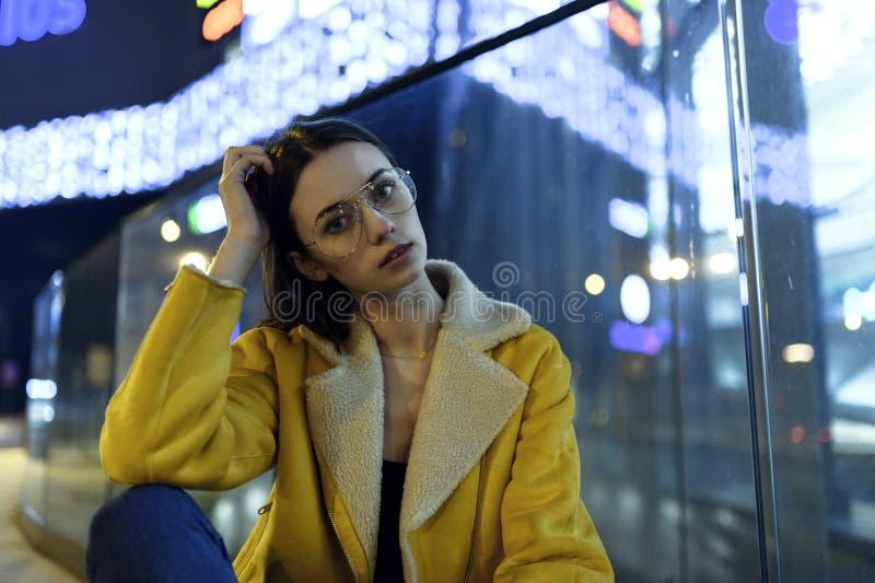 Портрет модели моды женской представляя в желтой куртке и стеклах, в светах города к ночь Стиль Womenswear стоковая фотография rf