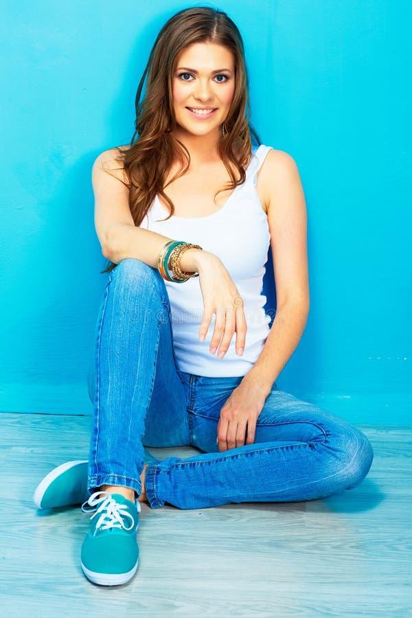 Портрет модели стиля подростка женской усмехаясь сидя на floo стоковая фотография rf