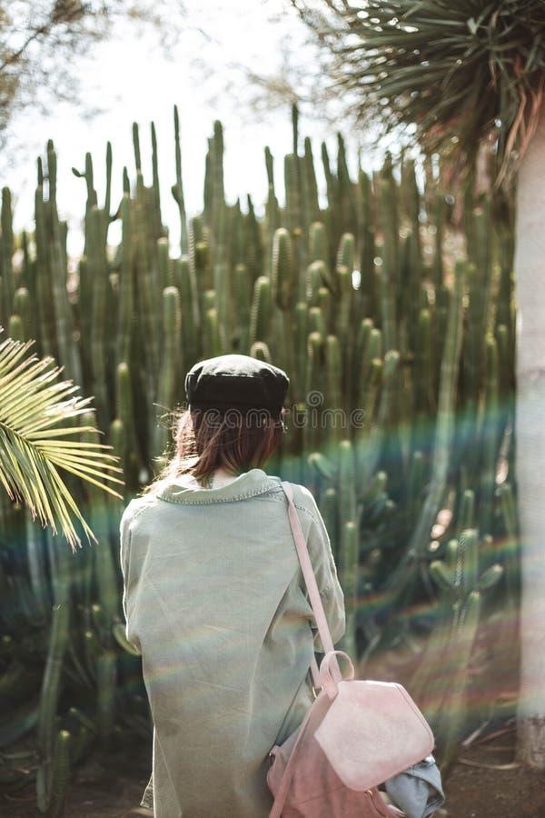 Портрет модели с черной крышкой среди кактуса стоковое фото