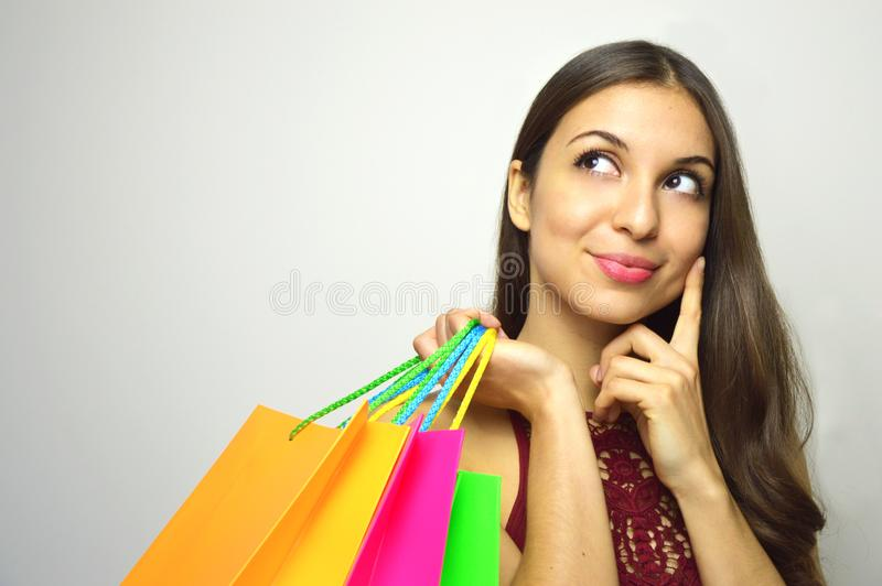 Портрет модного шикарного брюнет при покупатель сумок в ее руке думая что купить и смотря к стороне sp экземпляра стоковая фотография