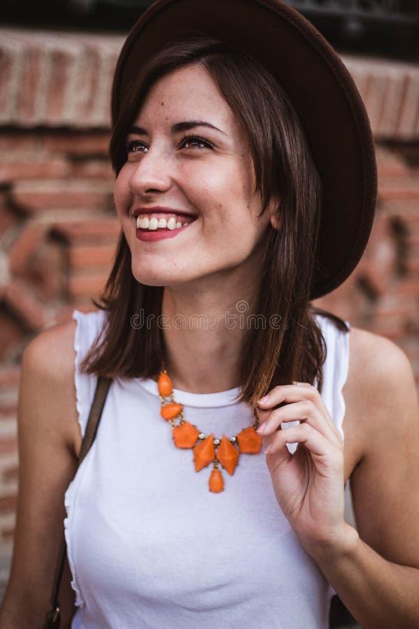 Портрет модной женщины с аксессуарами держа шляпу с улыбкой стоковые фотографии rf