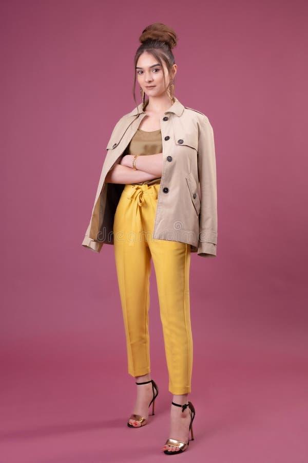 Портрет модной молодой женщины одетый в желтых брюках стоковые изображения rf