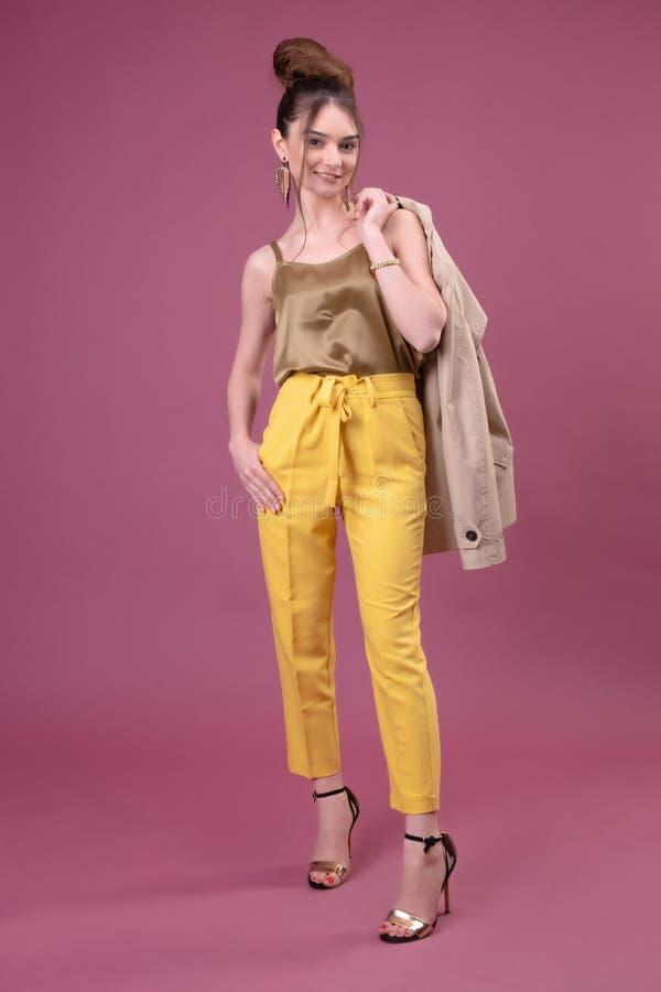 Портрет модной молодой женщины одетый в желтых брюках стоковое фото rf