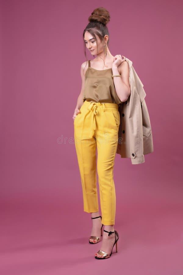 Портрет модной молодой женщины одетый в желтых брюках стоковые фото