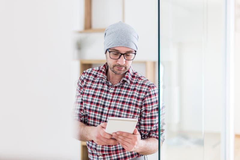 Портрет модных архитектора или дизайнера с прибором планшета стоя на офисе стоковое изображение rf